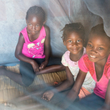 Children playing under mosquito net in RBM newsletter